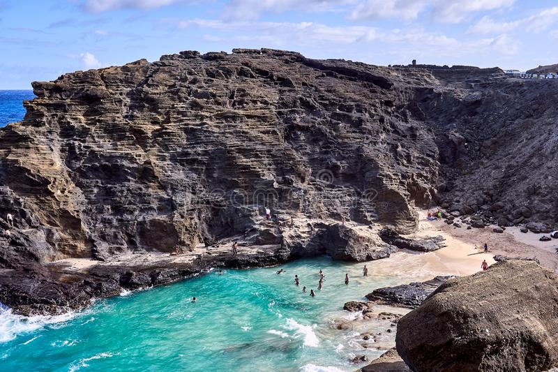 Hawaii, USA - August 5, 2017 : People enjoying the waves and the ocean at a secluded beach surrounded by rocky cliffs. Hawaii, USA - August 5, 2017 : Many people stock photography