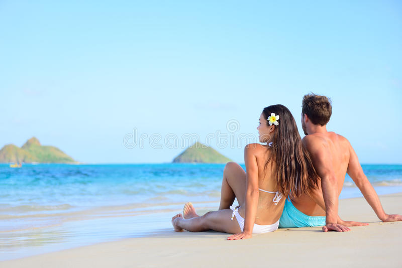 Hawaii vacation couple relaxing tanning on beach stock photo