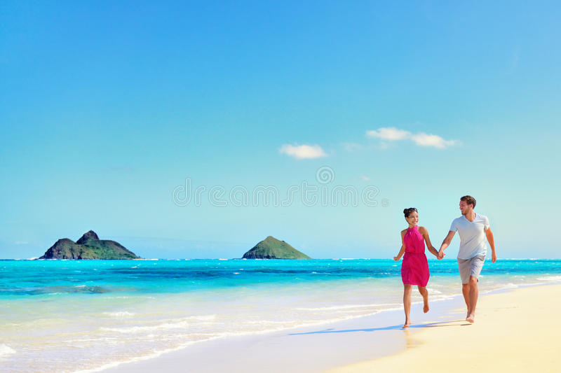 Hawaii vacation couple walking on turquoise beach stock for Where to go for a white christmas in usa
