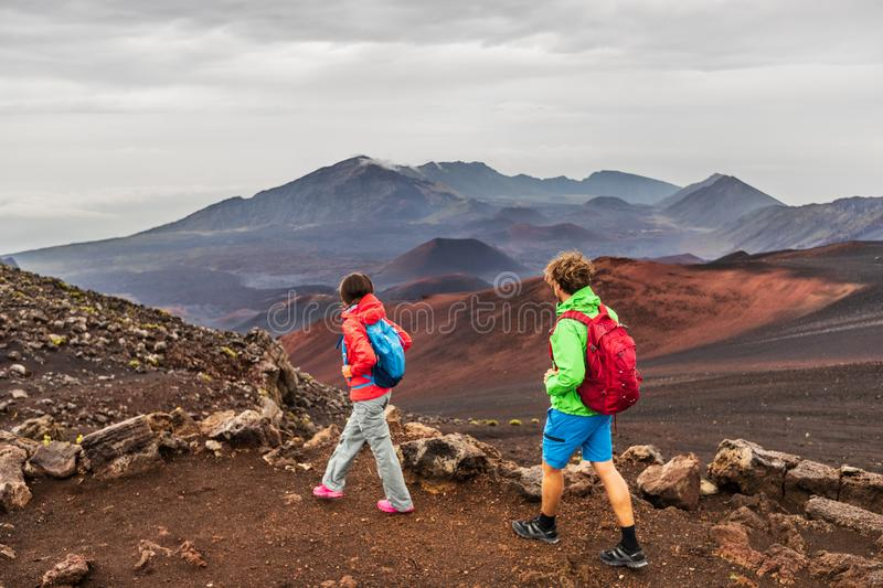 Hawaii volcano hikers people walking hiking on mountains in Haleakala volcanic background landscape. Two young tourists couple on stock photo