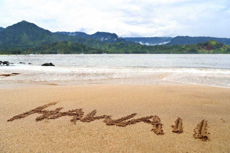 Hawaii-Wort geschrieben auf Sand auf hawaiischem Strand lizenzfreies stockbild