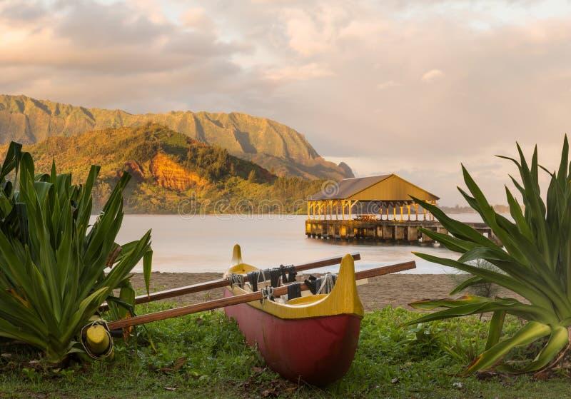 Hawaiiaanse kano door Hanalei Pier stock fotografie