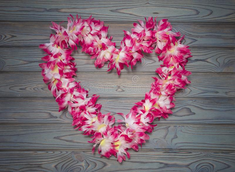 Hawaiiaanse kroon van bloemen in de vorm van hart op een blauwe houten achtergrond stock foto