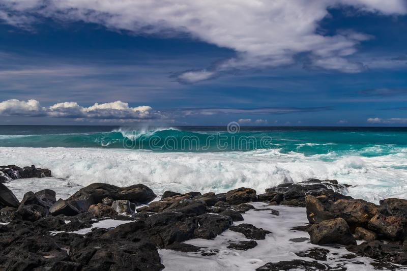 Hawaiian beach; volcanic rocks and form on shoreline; wave breaking offshore. Pacific, blue sky and clouds in distance. stock photo