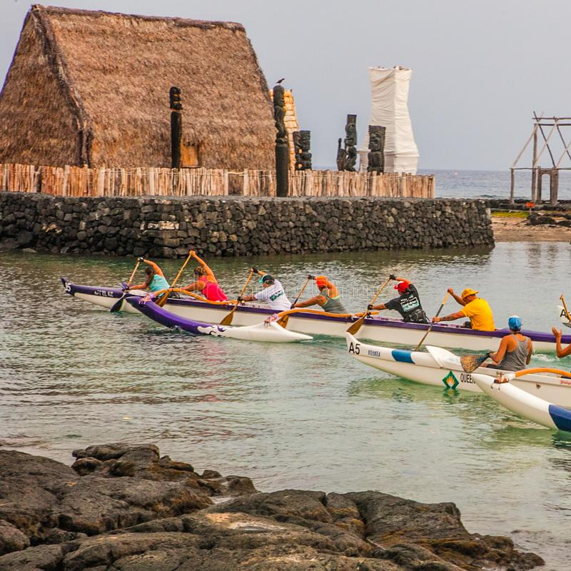 Hawaiian canoes men peddle religious building floatinf stock images