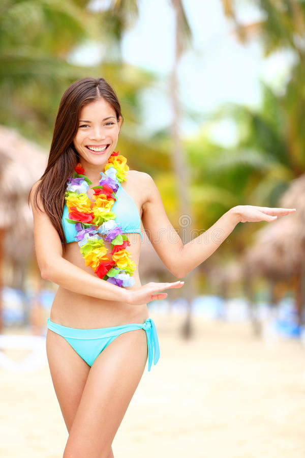 Hawaiian dance - hula dancer. Vacation concept with beautiful mixed race Asian / Caucasian young woman dancing on tropical beach stock images