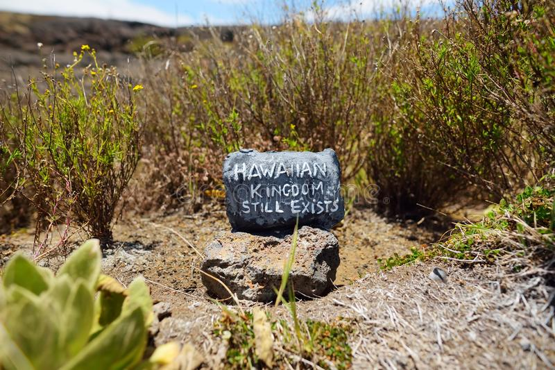 `Hawaiian Kingdom still exists` stone sitting on frozen lava after Mauna Loa volcano eruption royalty free stock photo