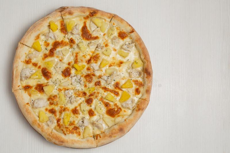 Hawaiian pizza with chicken, pineapple and cheese, on a white wooden table, close-up shot royalty free stock photos