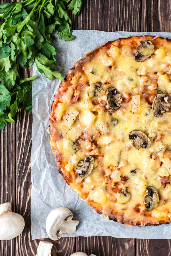 Hawaiian pizza with meat, mushrooms and pineapple on a wooden ba. Delicious Hawaiian pizza with meat, mushrooms and pineapple on a wooden background royalty free stock image