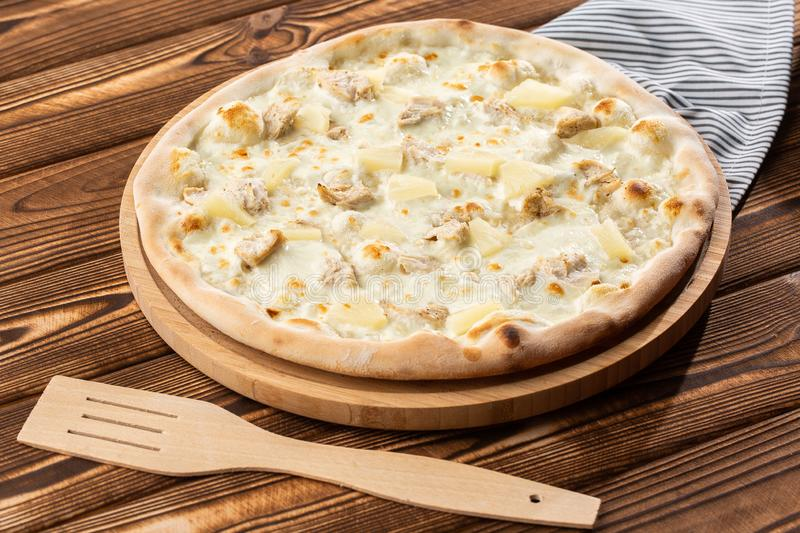Pizza topped with sauce, chicken, cheese and pineapple serve on wooden plate on wooden table. Photo of Hawaiian pizza. stock photos