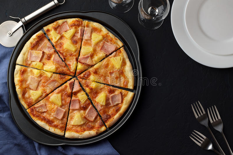 Hawaiian pizza with sweet pineapple and salty ham on dark stone background with plates, forks and glasses. stock photo