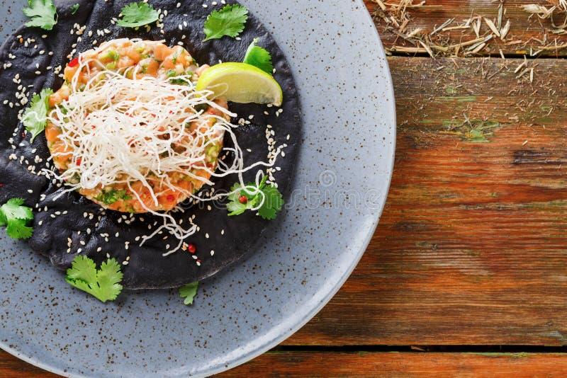 Hawaiian poke on black sesame flat cake. Modern restaurant food background stock photos