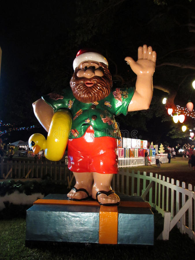 Hawaiian Santa Figures holds rubber ducky as he waves stock images