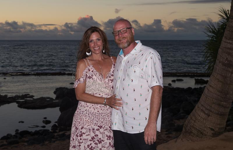 Hawaiian tourists on vacation. Man and women together at ocean sunset royalty free stock images
