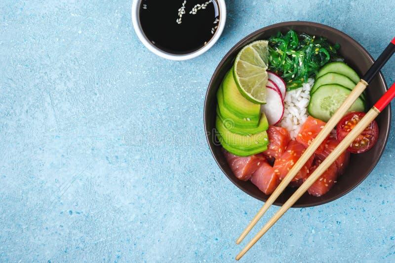 Hawaiische Lachse stoßen Salat mit Reis, Gemüse und Meerespflanze auf blauem Hintergrund lizenzfreie stockfotos