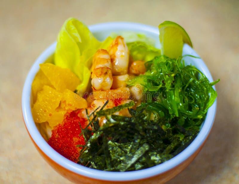 Hawaiische Lachse stoßen Schüssel mit Meerespflanze, Avocado stiegen, Samen des indischen Sesams und Schalotten Draufsicht, obenl stockfoto
