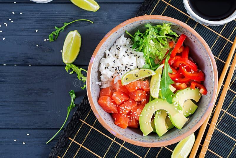 Hawaiische Lachsfischstoßschüssel mit Reis, Avocado, Paprika, Samen des indischen Sesams und Kalk stockfoto