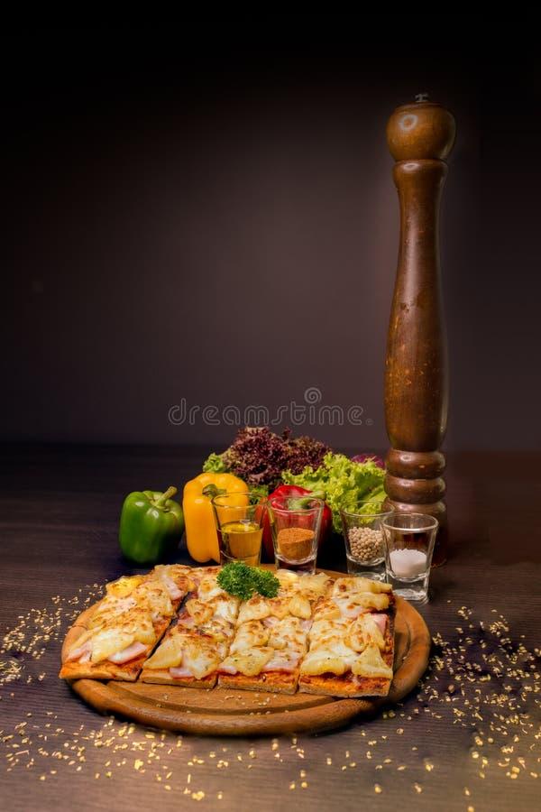 Hawaiische Pizza diente auf hölzernen Beschaffenheitsplatten verzieren mit Fruchtgemüse und Papiermühle lizenzfreie stockbilder