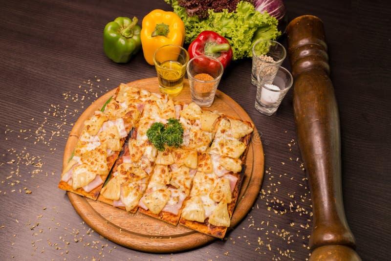 Hawaiische Pizza diente auf hölzernen Beschaffenheitsplatten verzieren mit Fruchtgemüse und Papiermühle lizenzfreies stockbild