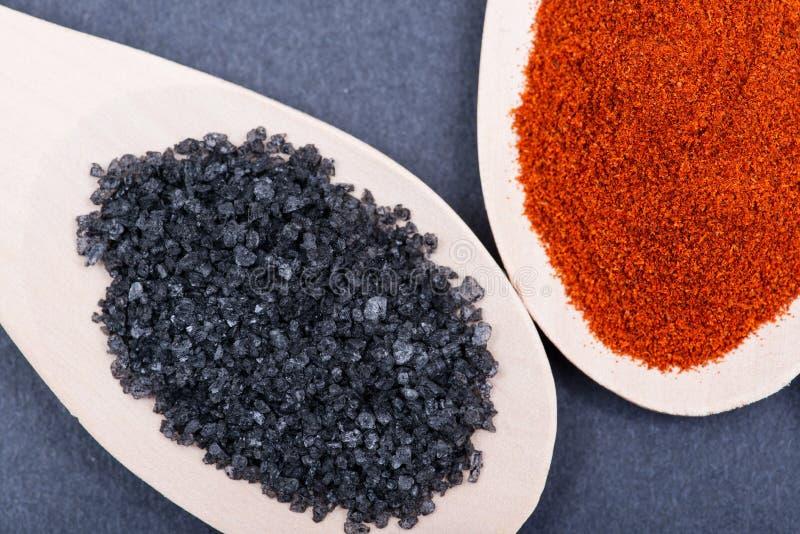 Hawaiisches schwarzes Lava Sea Salt und getrocknetes organisches süßes Paprikapulver in den handgemachten hölzernen Löffeln auf D stockfotografie