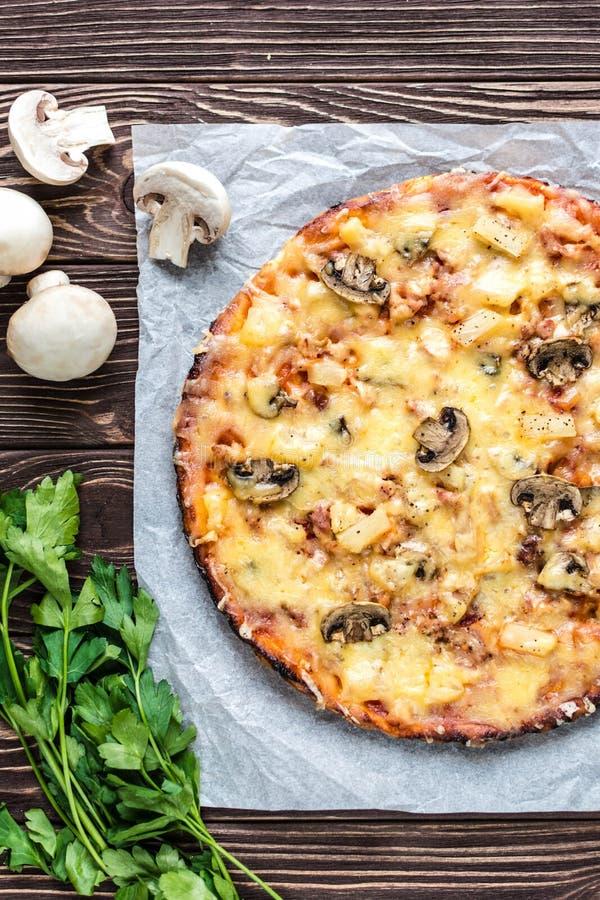 Hawajska pizza z mięsem, pieczarkami i ananasem na, drewniani półdupki zdjęcie royalty free