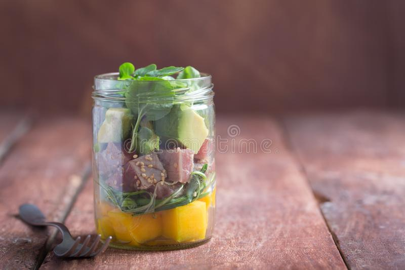 Hawajska potrącenie sałatka z tuńczykiem, avocado i warzywami w słoju na drewnianym nieociosanym tle, obraz stock
