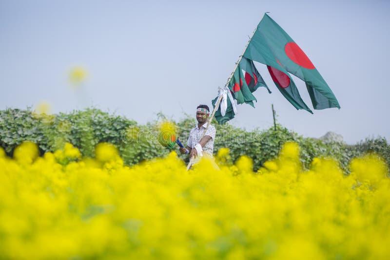 A Hawker sells Bangladeshi national flags at mustard field at Munshigonj, Dhaka, Bangladesh. Hawker petty traders paddling in cities and rural areas. In stock images