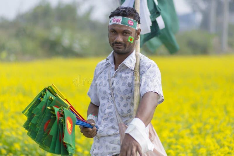 A Hawker sells Bangladeshi national flags at mustard field at Munshigonj, Dhaka, Bangladesh. Hawker petty traders paddling in cities and rural areas. In stock photos