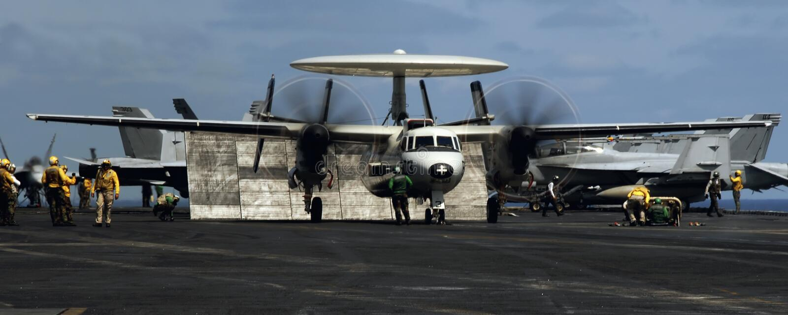 Hawkeye Run Up. An E-2C Hawkeye prepares to launch from a busy aircraft carrier deck royalty free stock photo