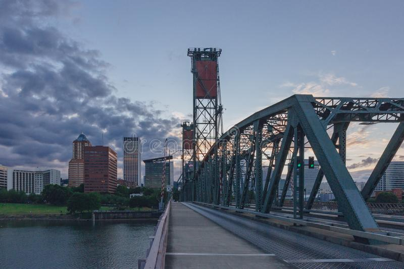 Hawthorne Bridge over Willamette River at sunset with skyline of downtown Portland, USA. View of Hawthorne Bridge over Willamette River at sunset with skyline of stock image