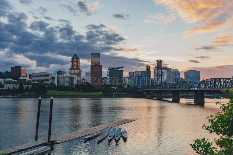 Hawthorne Bridge over Willamette River at sunset with skyline of downtown Portland, USA. View of Hawthorne Bridge over Willamette River at sunset with skyline of royalty free stock image