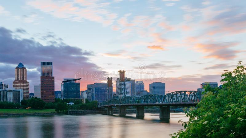 Hawthorne Bridge over Willamette River at sunset with skyline of downtown Portland, USA. View of Hawthorne Bridge over Willamette River at sunset with skyline of stock photography