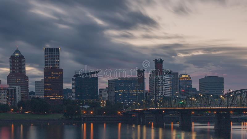 Hawthorne Bridge over Willamette River at sunset with skyline of downtown Portland, USA. View of Hawthorne Bridge over Willamette River at sunset with skyline of royalty free stock photography