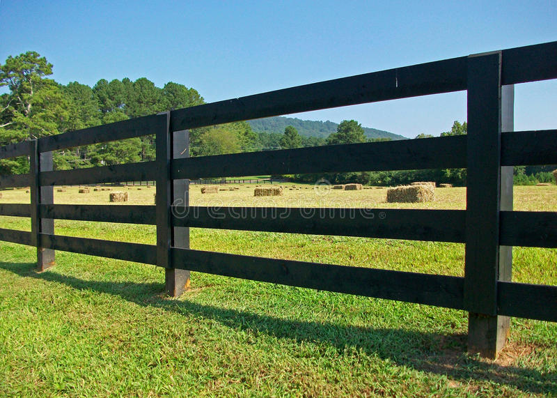 Hay Bales Through the Fence. Bales of hay visible through the slats of a black rail fence stock photo