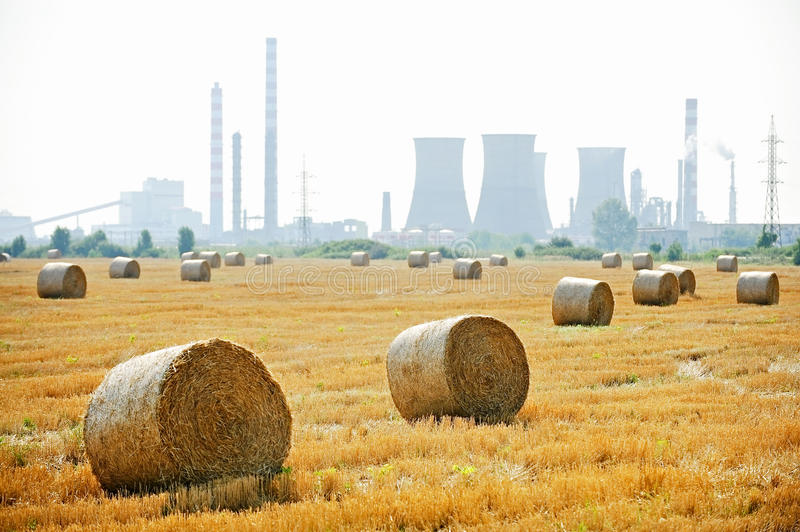 Hay bales with petrochemical plant on background royalty free stock images