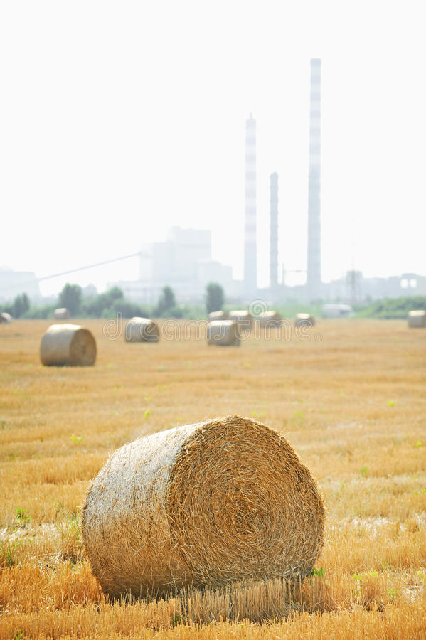 Hay bales with petrochemical plant on background stock photography