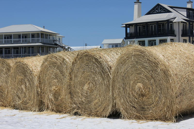Hay bales on white sand beach for oil cleanup royalty free stock photography
