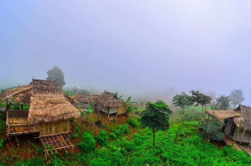 Hay casas en Akha ubicadas en una ladera cubierta de ladera y de fondo niebla en Doi Sa Ngo, Chiang Rai , Tailandia fotografía de archivo