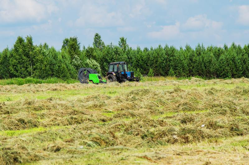 Hay harvesting with the help of special equipment. Tractor with baler discharges for hay harvesting in the field royalty free stock photography