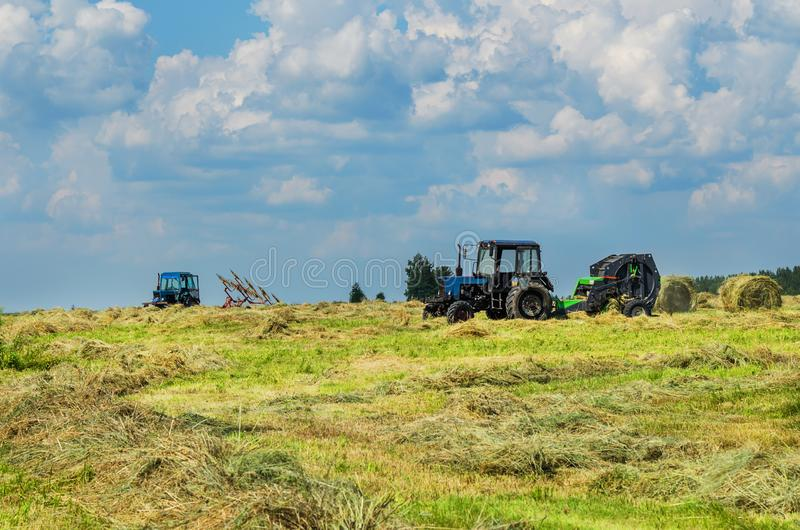 Hay harvesting with special equipment. Tractor with baler discharges for hay harvesting, and with mechanized rake in the field royalty free stock photos