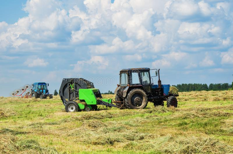 Hay harvesting with special equipment. Tractor with baler discharges for hay harvesting, and with mechanized rake in the field royalty free stock image