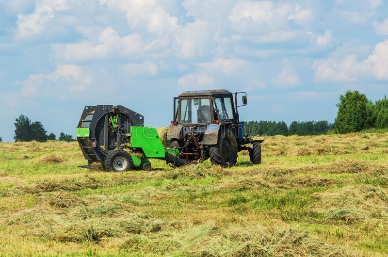 Hay harvesting on a summer day. Tractor with pick-up for hay harvesting in the field on a summer evening royalty free stock images