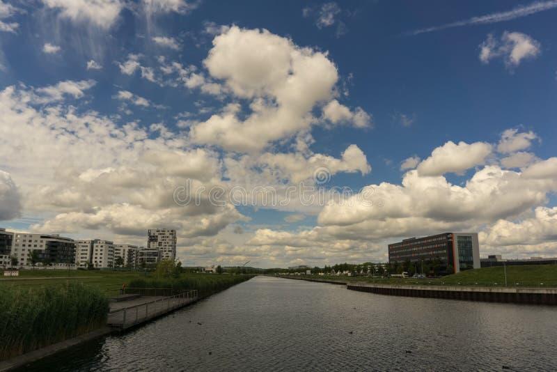 Hay muchas nuevas construcciones de viviendas, un pequeño río y algunos edificios industriales foto de archivo libre de regalías