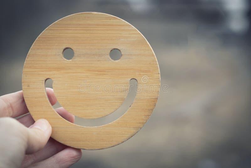 Hay un buen humor cuando hay limpieza y ecología alrededor La mano lleva a cabo el smilie redondo de madera en fondo borroso de l fotografía de archivo libre de regalías