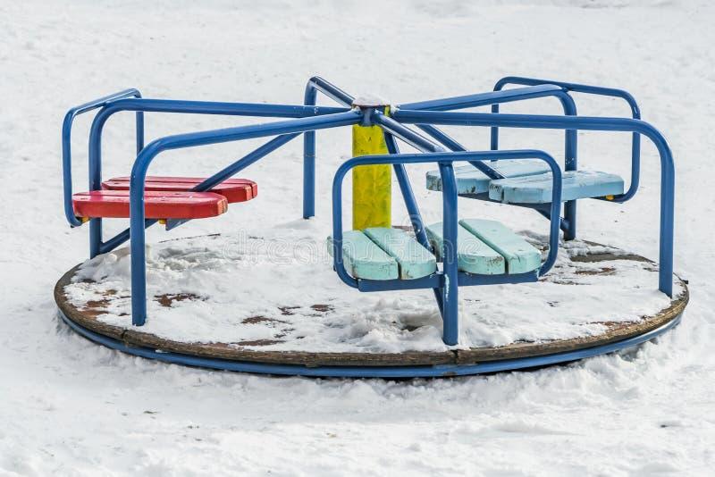 Hay un carrusel del metal y de la madera pintados con la pintura colorida con la nieve blanca en un patio de los niños en el pati imagen de archivo