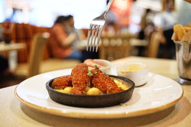 Hay una bifurcación sobre el pollo sin hueso frito crujiente y el queso derretido contenidos en la cacerola de acero caliente ser imagen de archivo