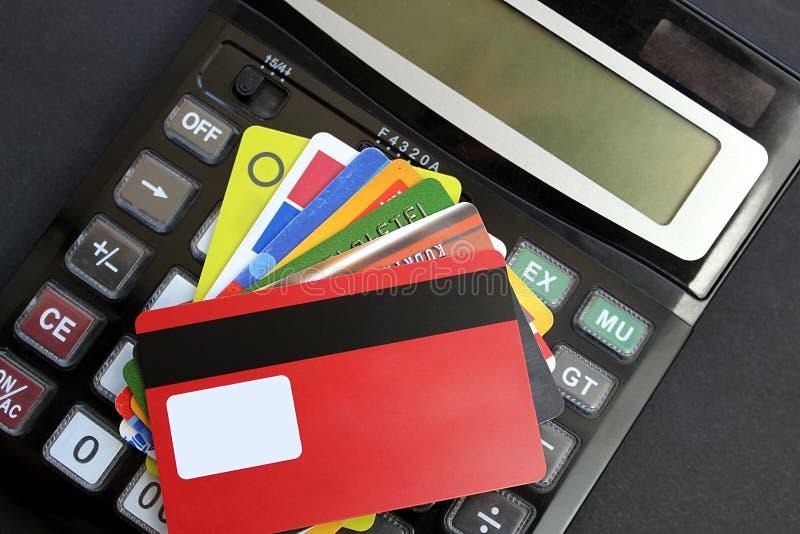 Hay varias tarjetas de banco plásticas en la calculadora fotografía de archivo