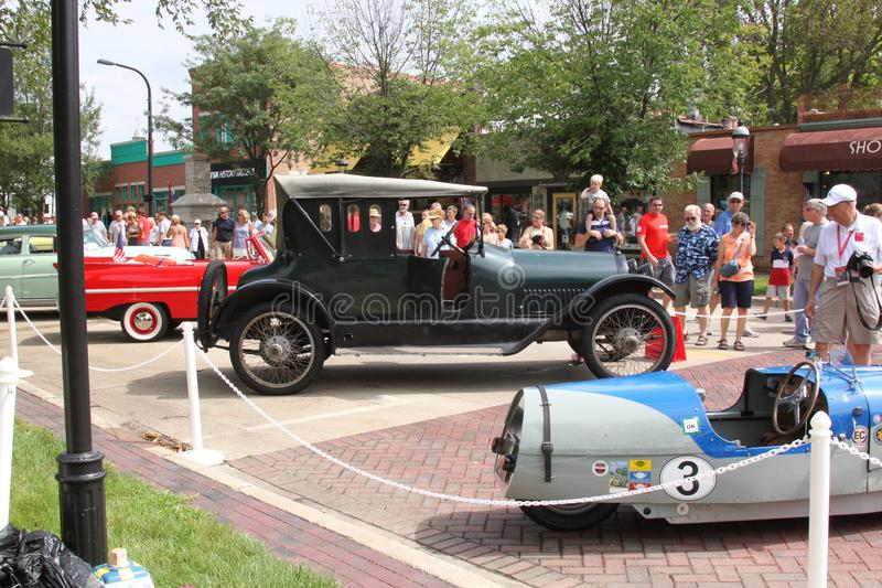 1916 Haynes Clover Leaf Roadster. The 1916 Haynes Clover Leaf Roadster between two other rare automobiles in a line of automobiles, with passersby marveling at royalty free stock images