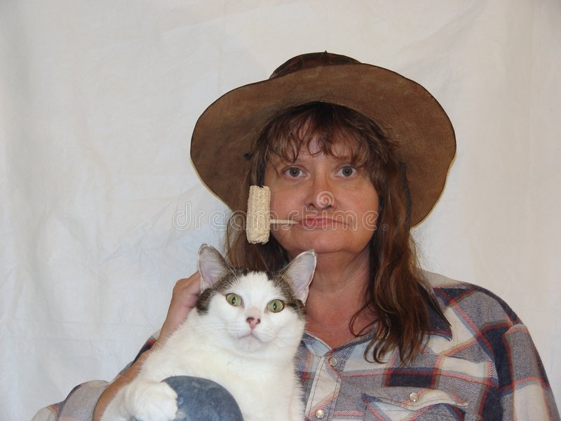 Hayseed and fat cat. Country bumpkin woman and fat cat royalty free stock image
