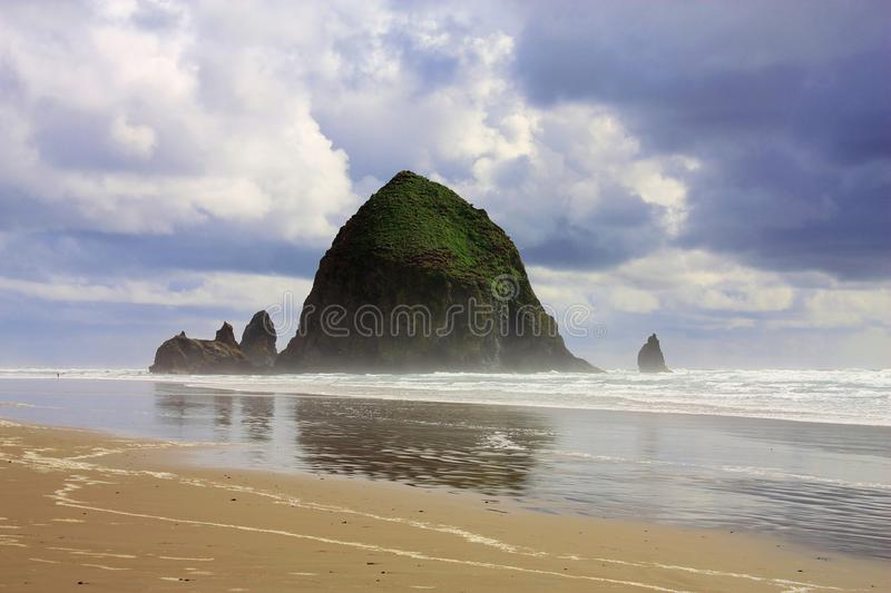 Dramatic Spring Day at Haystack Rock on Cannon Beach along the Pacific Coast of Oregon, USA. Haystack Rock is one of the massive seastacks sitting off the coast stock image